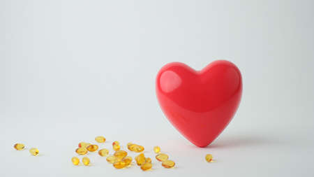 red heart on white background with the supplement. Zdjęcie Seryjne