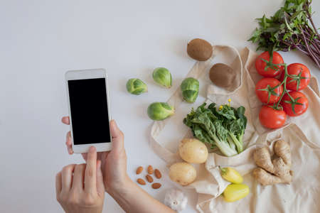 hands and mobile phone for searching online app for recipe , nutrition, diet and grocery shopping. Zdjęcie Seryjne - 153015215