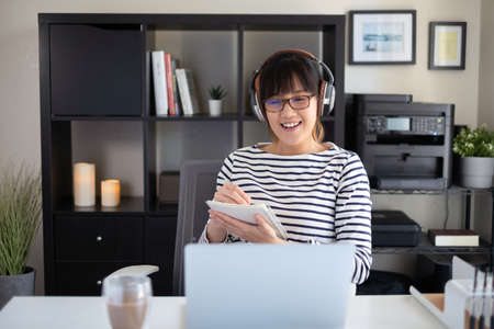 college student learning online class looking at the camera on computer screen. remote course for university education. happy and smile asian woman. Zdjęcie Seryjne - 154450616