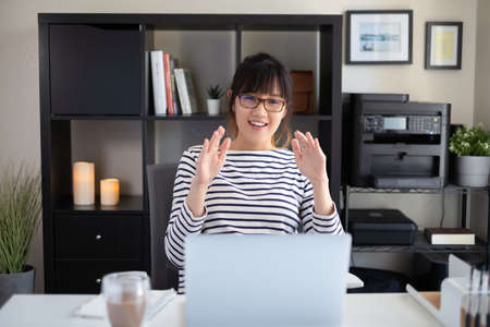 college student learning online class looking at the camera on computer screen. remote course for university education. happy and smile asian woman.