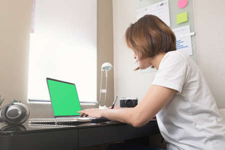 woman looking at the computer green screen for online class learning.