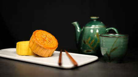 Moon cake with tea. Chinese celebration and asian tradition. Baked oriental pastry for mid autumn. 版權商用圖片