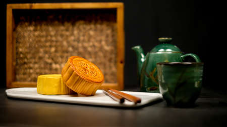 Moon cake with tea. Chinese celebration and asian tradition. Baked oriental pastry for mid autumn. Imagens