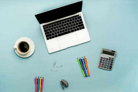 office supplies on a blue background. study online and work with the laptop concept.