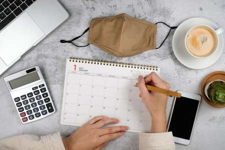 hand writing on planner and Calendar for2021. Online work plan with mask and new normal life .