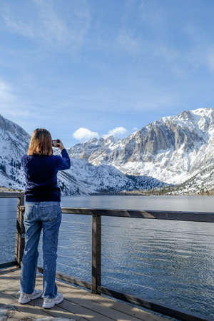 travel woman use smart phone o taking photo of the beautiful mountain landscape. Imagens