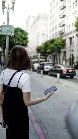 asian woman hipster travel and using the mobile phone in the city street.