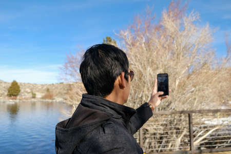 travel man use smart phone o taking photo of the beautiful mountain landscape.