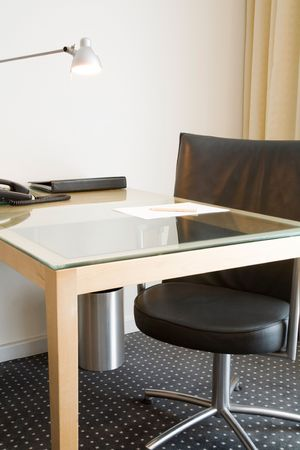 Desk with lamp and black leather swivel chair. Could depict an office desk, home study or hotel room. Stock Photo - 4358467