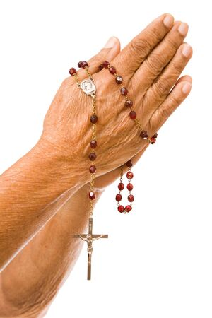 An old asian woman holds her hands in prayer with a rosary Stock Photo