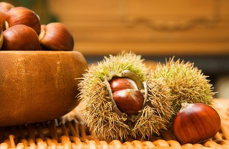 heaped: Autumnal arrangement with a bowl of chestnuts in front of a fireplace
