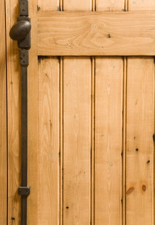 Detail of wooden panelled furniture with iron handle photo
