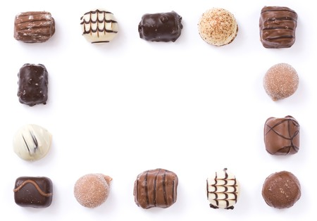 Border of individual chocolates isolated on white with copy space