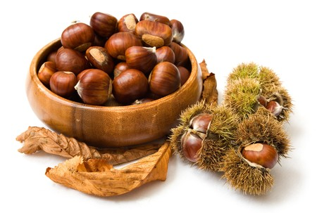 Autumnal arrangement with a bowl of chestnuts isolated on white photo