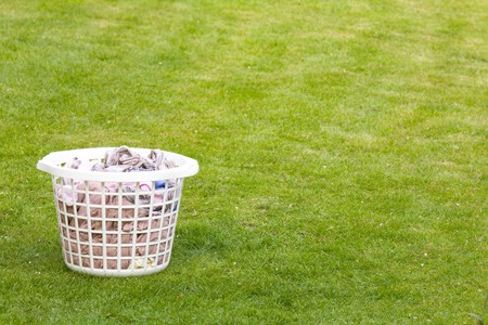 creased: Laundry basket filled with clothes on lawn with copy space