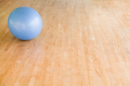 Swiss ball on a wooden gym floor with copy space photo