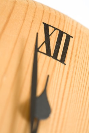 Closeup of a wooden clock with hands approaching midnight photo