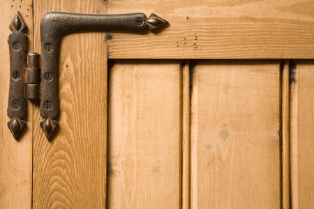 closeups: Detail of wooden panelled furniture with iron hinge