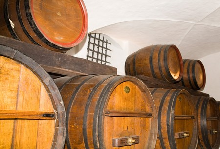 Wine ages in a cellar with traditional oak wine barrels photo