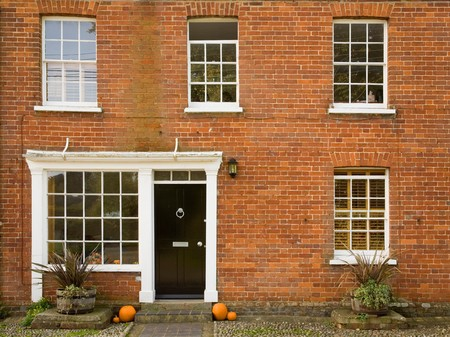 doorstep: Front of a traditional house with halloween pumpkins on the doorstep Stock Photo