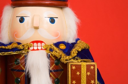 A traditional Christmas nutcracker ornament isolated on red photo