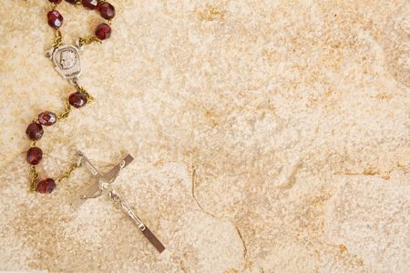 Rosary beads on a sandstone background
