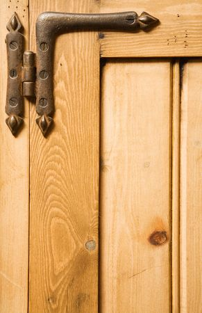 Detail of wooden panelled furniture with iron hinge photo