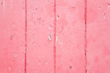 Closeup of wood panels with peeling pink paint photo