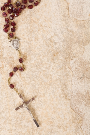 Rosary beads on a sandstone background with space for text