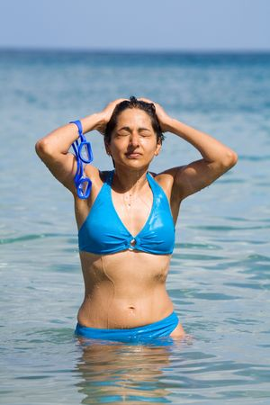 An Indian woman in blue bikini with swimming goggles bathes in the sea. photo