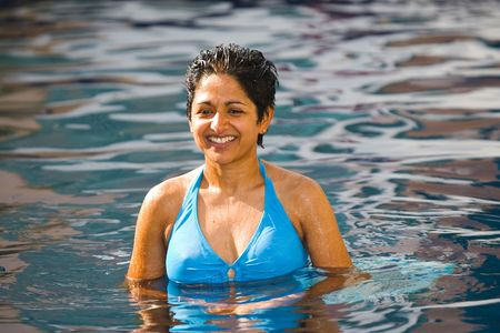 An athletic looking Asian  Indian woman in blue bikini stands smiling in a swimming pool photo