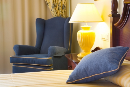 Detail of a luxury hotel bedroom featuring bed, chair and bedside lamp