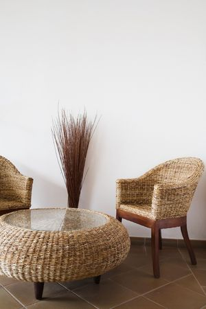 Wicker table and chairs against a white wall with copy space
