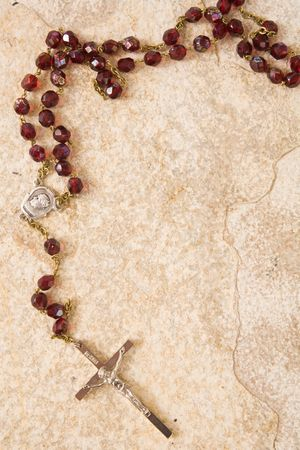 roman catholic: Rosary beads on a sandstone background with space for text