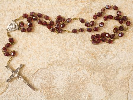 religious text: Rosary beads on a sandstone background with space for text