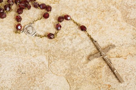 roman catholic: Rosary beads on a sandstone background
