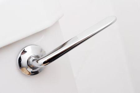Chrom-flush-Handle auf einer weißen Toilette