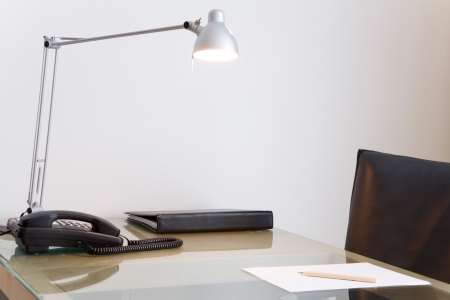neat: Desk with lamp and black leather swivel chair. White wall in the background.