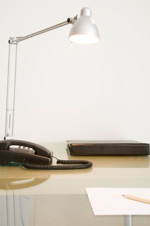 tidy: Cropped office desk with phone, lamp and note pad against white wall.
