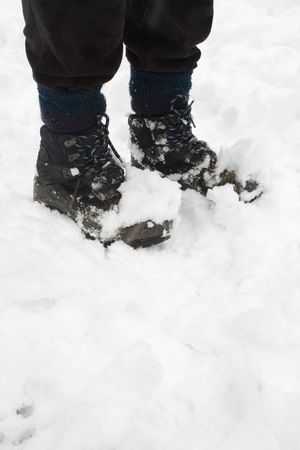 Womans hiking boots covered in snow, closeup with copy space photo