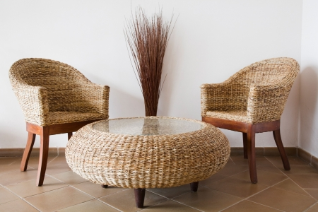 den: Rattan patio furniture against a white wall Stock Photo
