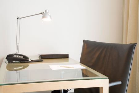 home office desk: Desk with lamp and black leather swivel chair. Could depict an office desk, home study or hotel room.