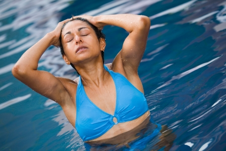 An athletic Indian woman in blue bikini relaxes in a swimming pool Stock Photo - 6121438