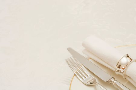 dining out: Knife and fork with napkin and plate, on a tablecloth with copyspace Stock Photo