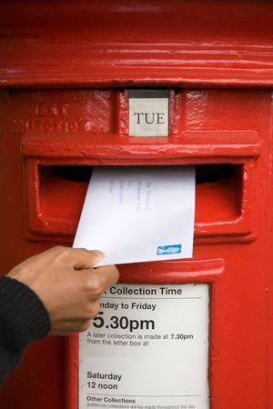 comunicaci�n escrita: Una mujer env�a una carta en un buz�n tradicional brit�nico de rojo