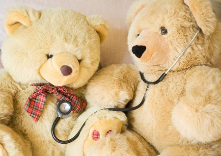 doctor toys: Teddy bears with stethoscope posing as doctor and patient. Ideal to illustrate paediatrics. Stock Photo