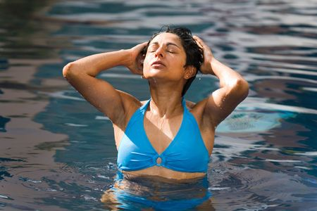 An athletic Indian woman in blue bikini relaxes in a swimming pool photo