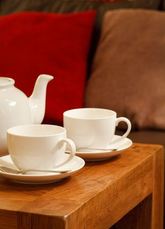 Teapot and cups on a table in a cozy den photo