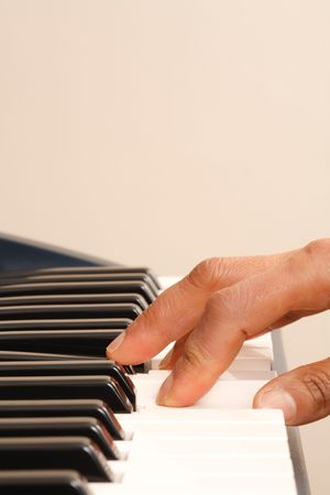Closeup of a hand playing on a piano keyboard with copyspace photo