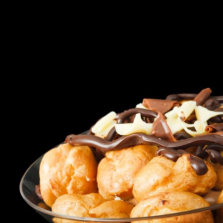 smothered: Bowl of profiteroles smothered in chocolate, isolated against a black background with copy space